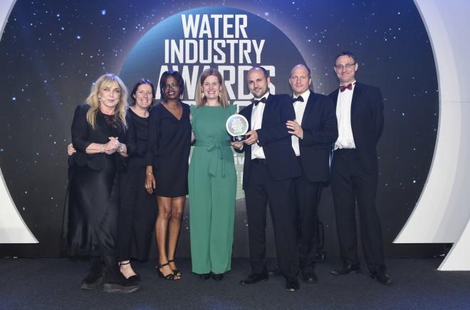 Isle Utilities and Aimen receiving the award [left to right: Helen Lederer (host); Elvira Serra (Isle); Babi Uku (Isle); Blanca Antizar (Isle), Ambroise Vandewynckele (Aimen); Piers Clark (Isle); James Brockett (WWT)]